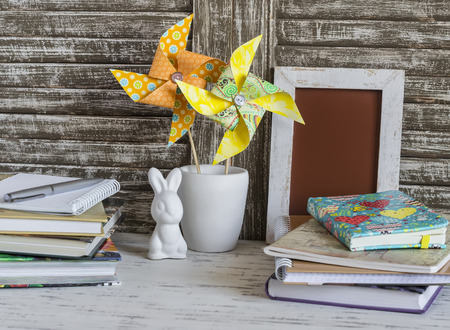 pinwheels: Childrens home workspace with books, notebooks, notepads and handmade paper pinwheels and easter ceramic bunny. Stock Photo