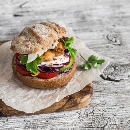 Homemade crispy fish burger on a light rustic wooden board 版權商用圖片
