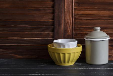 rustic kitchen: Rustic kitchen still life. vintage ceramic bowl and enameled jar on dark wooden table