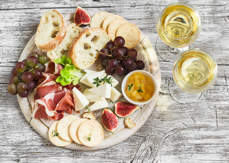 delicious appetizer to wine - ham, cheese, grapes, crackers, figs, nuts, jam, served on a light wooden board, and two glasses with white wine on bright wooden surface
