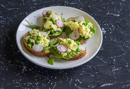 Huevo revuelto sándwich con guisantes y rábanos en un fondo de piedra oscura. Comida sana y deliciosa