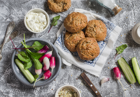 multi grain sandwich: Homemade whole grain rolls, cottage cheese, fresh vegetables - radishes, cucumbers, lettuce on a grey stone background. Healthy snack in a rustic style. Top view Stock Photo