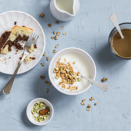 oatmeal: Breakfast - greek yogurt with granola and pistachios, chocolate cake and coffee. On a blue stone background