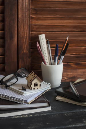 building planners: Workplace designer and architect with business objects - books, notebooks, pens, pencils, rulers, tablet, glasses and a model of a wooden house. Planning of the construction of a house. Stock Photo