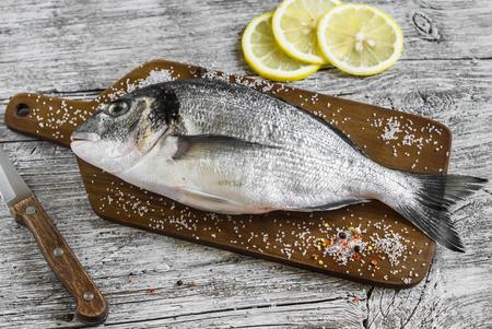rustic food: Fresh raw Dorado fish on wooden rustic background. Healthy food