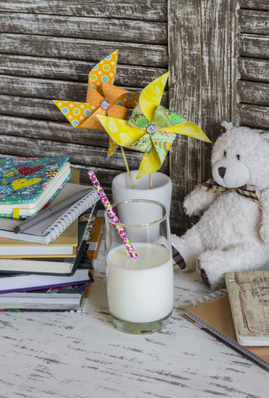 pinwheels: Homemade baby workplace with books, notebooks, journals, handmade paper pinwheels and a glass of milk