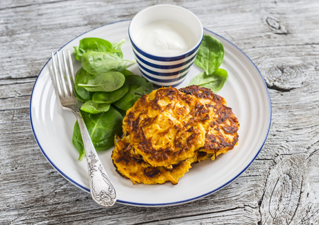Sweet potato pancakes and fresh spinach on a light wooden background