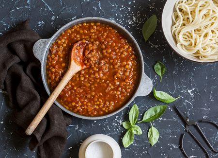 bolognese sauce: Vegetarian lentil bolognese sauce in a frying pan on a dark background.