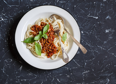 Spaghetti with vegetarian lentil bolognese on a dark background. Delicious healthy vegetarian food