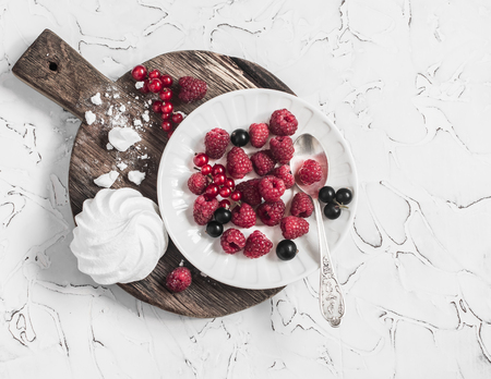 black currants: Raspberries, red and black currants, a meringue on a rustic cutting board, on bright background Stock Photo