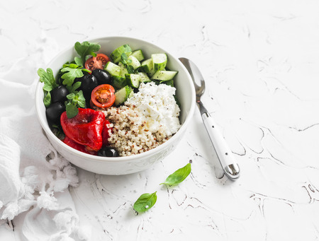 Mediterranean quinoa bowl with avocado, cucumbers, olives, tomatoes, feta cheese, arugula. On a white background. Delicious healthy vegetarian food