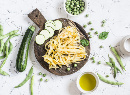 Dry pasta tagliatelle, zucchini, green beans and peas, olive oil on a light background. Vegetarian food