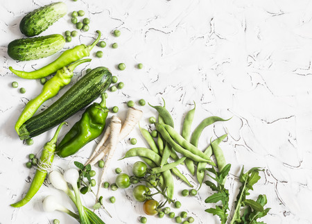 parsnips: Fresh green vegetables - zucchini, cucumbers, green peas and beans, parsnips, peppers, tomatoes, onions on a white background. Vegetarian, vegan table Stock Photo