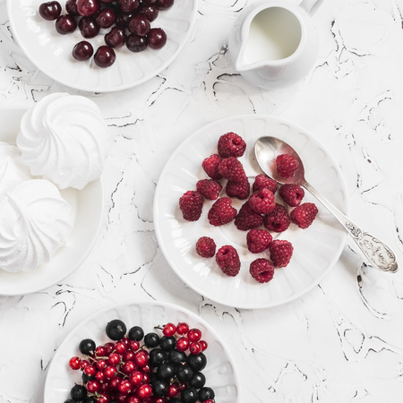 black currants: Raspberries, red and black currants, cherry, a meringue, cream on light background