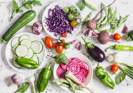 Assortment of fresh vegetables on a light background - zucchini, eggplant, peppers, beets, tomatoes, green beans, red cabbage. Free space for text, top view. Cooking background