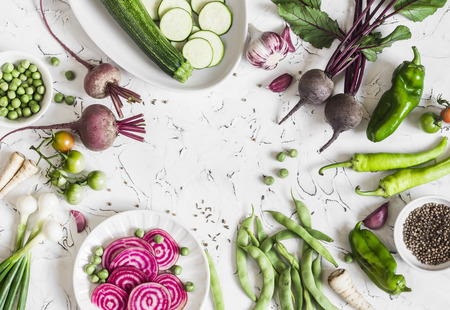 Fresh raw vegetables - beets, green peas and beans, zucchini, peppers, onions, garlic, spices on a light background. Cooking background, space for text. Top view Banco de Imagens
