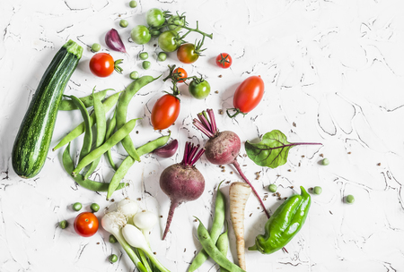 Assortment of fresh vegetables on a light background - zucchini, peppers, beets, tomatoes, green beans, onion. Food background. Free space for text, top view