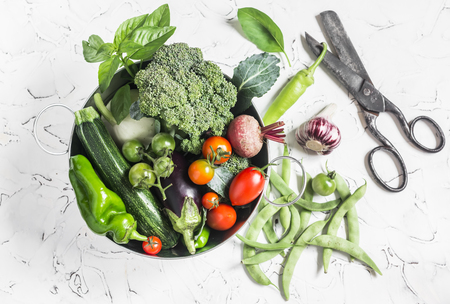 berenjena: verduras frescas - brócoli, calabacín, remolacha, pimientos, tomates, judías verdes, el ajo, la albahaca en una cesta de metal sobre un fondo claro. Comida sana