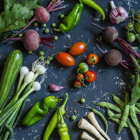 Beets, zucchini, peppers, onion, garlic, green beans, beans, tomatoes, parsnips, parsley - fresh vegetables on a dark background. Raw ingredients. Top view Stock Photo