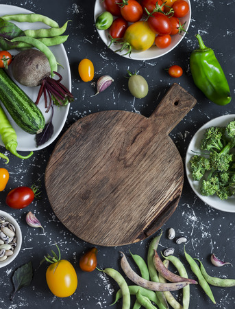 Food background. Assortment of fresh vegetables around the cutting board on a dark background. Top view, free space for text
