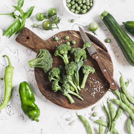 Frisches grünes Gemüse - Brokkoli, Zucchini, grüne Erbsen und Bohnen, Paprika auf Holzbrett auf hellem Hintergrund. Vegetarisch, Diätkost