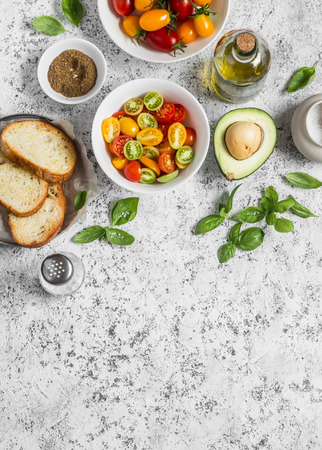 Ingredients for bruschetta - tomatoes, avocado, basil, olive oil, bread. On a light background, top view