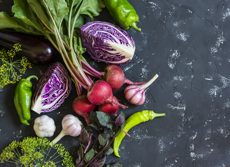 repollo: Fresh vegetables - red cabbage, beets, eggplant, peppers, garlic,  herbs on a dark background. Raw ingredients. Food background