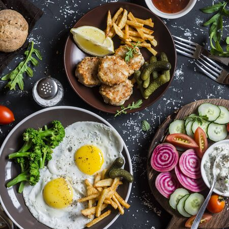 Lunch table - fried eggs, fish balls, potato chips, vegetables, sauces, homemade bread on a dark background. Rustic style, top view Stock Photo