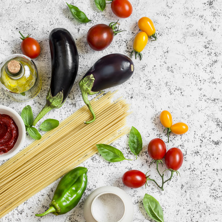 Raw ingredients for making pasta - spaghetti, eggplant, tomatoes, pepper, olive oil, tomato sauce and basil . Cooking background, top view