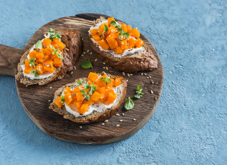 Pumpkin and goats cheese bruschetta on a wooden cutting board on blue background. Healthy vegetarian snack