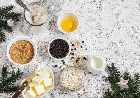 Christmas baking background. Flour, sugar, butter, rolled oats, eggs, chocolate chips on a light background. Baking ingredients