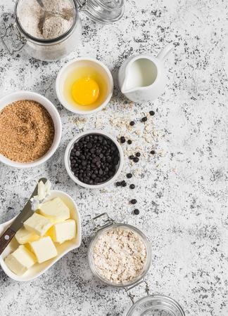 avena en hojuelas: hornear de fondo. Harina, azúcar, mantequilla, copos de avena, huevos, trocitos de chocolate sobre un fondo claro. ingredientes para hornear