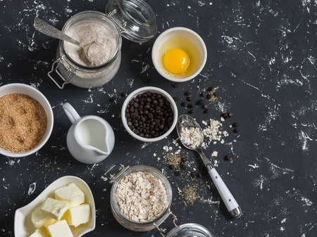 avena en hojuelas: Baking background. Flour, sugar, butter, rolled oats, eggs, chocolate chips on a dark background. Baking ingredients