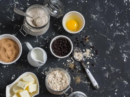 avena en hojuelas: hornear de fondo. Harina, azúcar, mantequilla, copos de avena, huevos, trocitos de chocolate sobre un fondo oscuro. ingredientes para hornear