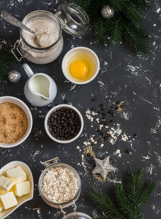 avena en hojuelas: Christmas baking background. Flour, sugar, butter, rolled oats, eggs, chocolate chips on a dark background. Baking ingredients