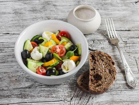 Greek salad on a rustic light wood background