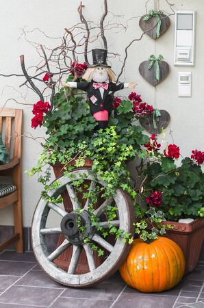 Halloween decoration - pumpkin, Scarecrow, old wooden wheel near the door of the house
