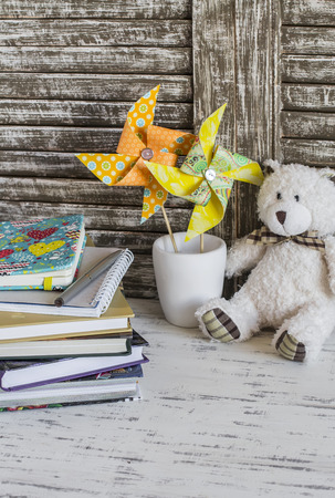 Childrens home workspace with books, notebooks, notepads, tablet and handmade paper pinwheels