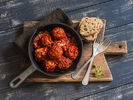 Meatballs in tomato sauce in a pan on rustic wooden cutting board on dark background