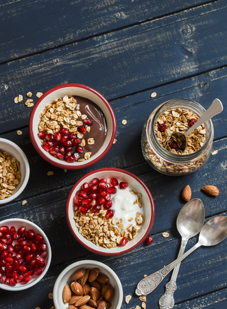breakfast bowl: Healthy Breakfast - yogurt with homemade granola and pomegranate on a dark wooden board. Top view