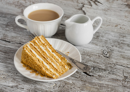 honey cake: piece of honey cake and tea with milk on the light rustic wooden table Stock Photo
