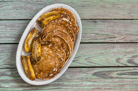 platanos fritos: Pancake with honey and fried bananas on a ceramic plate on a dark wooden background. Delicious breakfast or snack Foto de archivo