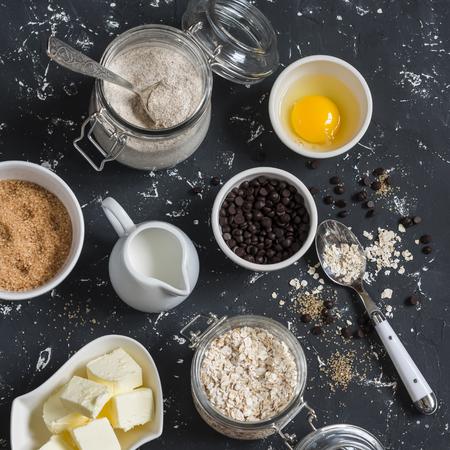 avena en hojuelas: Harina, azúcar, mantequilla, copos de avena, huevos, trocitos de chocolate sobre un fondo oscuro. ingredientes para hornear