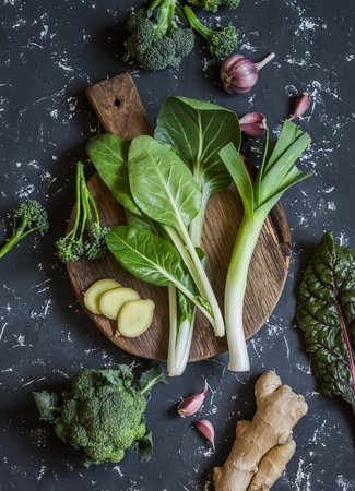Fresh ingredients -  chard, leeks, ginger, broccoli, garlic. On a dark background, top view