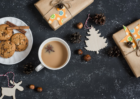 free christmas background: Christmas background - christmas homemade gifts, decorations, tea and biscuits. On a dark background, top view. Free space for text