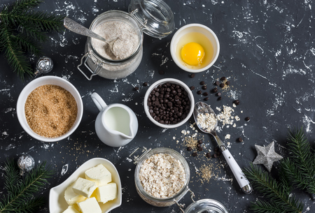rolled oats: Christmas baking background. Flour, sugar, butter, rolled oats, eggs, chocolate chips on a dark background. Baking ingredients