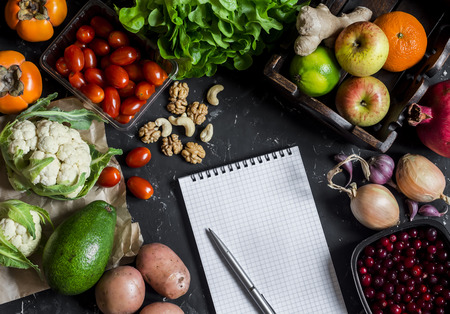 Assortment of fresh vegetables and fruit, clean Notepad on a dark background. Concept of a healthy diet and planning. Top view, flat lay
