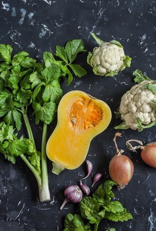 Fall vegetables on a dark background - pumpkin, cauliflower, celery, onion, garlic. Top view
