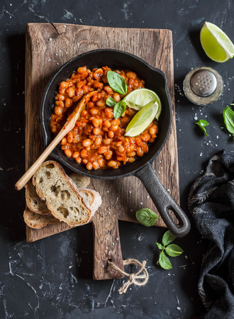 cast iron pan: Braised beans in tomato sauce in a cast iron pan and homemade bread on wooden cutting board. Stock Photo