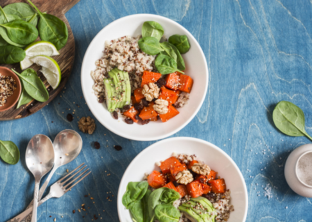 Quinoa with pumpkin, spinach and avocado. Healthy quinoa bowl. On a blue background, top view. Flat lay Imagens